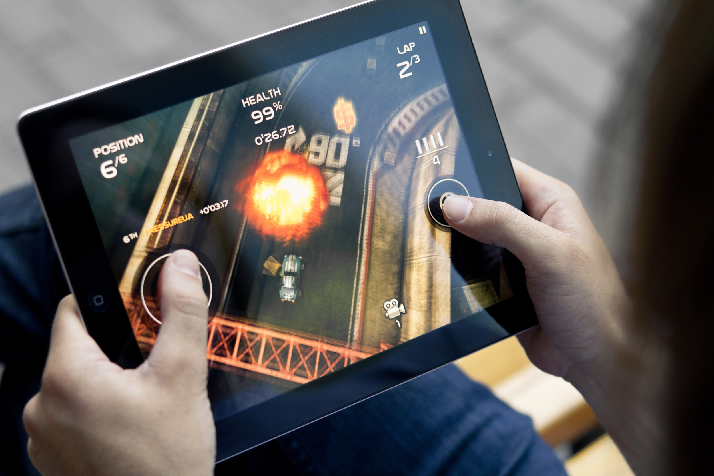 Man playing mobile game, Death Rally on a Apple iPad.